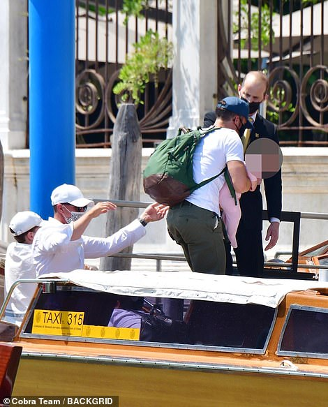 Drop off: Orlando held on to his daughter as he stepped off the boat, a green backpack over one shoulder