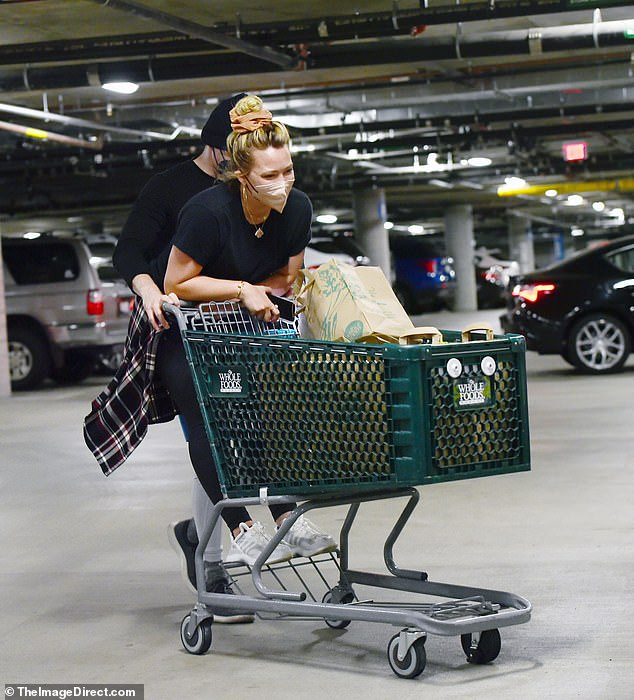 Loads of fun!Matthew pushed his wife forward as they made their way through the parking lot with their cart full of groceries