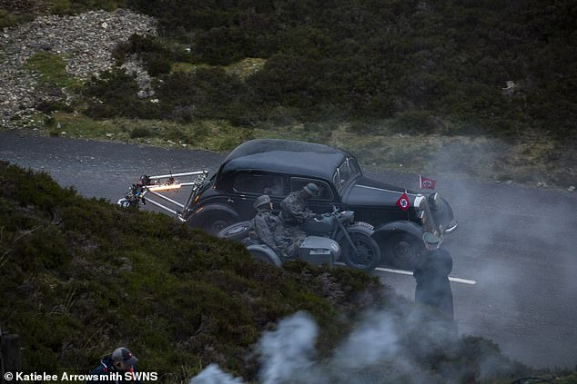 High-speed:Stunt drivers were seen racing along the road in a World War II car with Nazi flags on it
