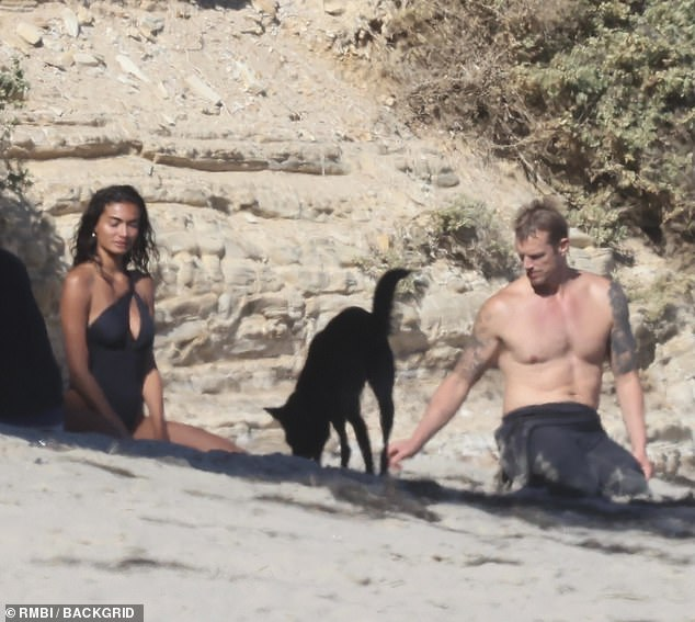 Action For All Mankind star Joel Kinnaman (right) adored his dog Zoe while his fiancee Kelly Gale (left) modeled swimsuits at a Malibu beach on Saturday