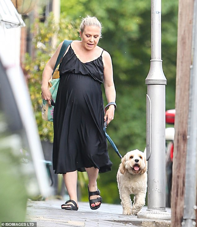 In the meantime: Pregnant EastEnders star Kellie Bright showed off her growing baby bump as she went out for a low-key dog walk in Hertfordshire on Wednesday