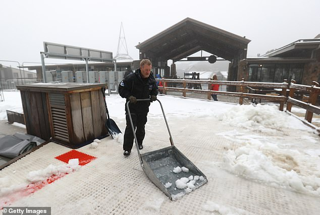 A lift operator shovels snow at Mt Buller Ski Resort on June 12. The resort had high hopes of a bumper season after being shut down by last year's disastrous Covid lockdown