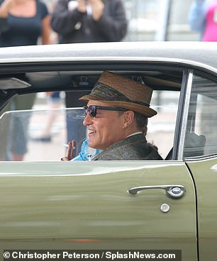 Driver's seat: Harrelson was decked out in a fedora and suit as he drove the vintage olive-green car