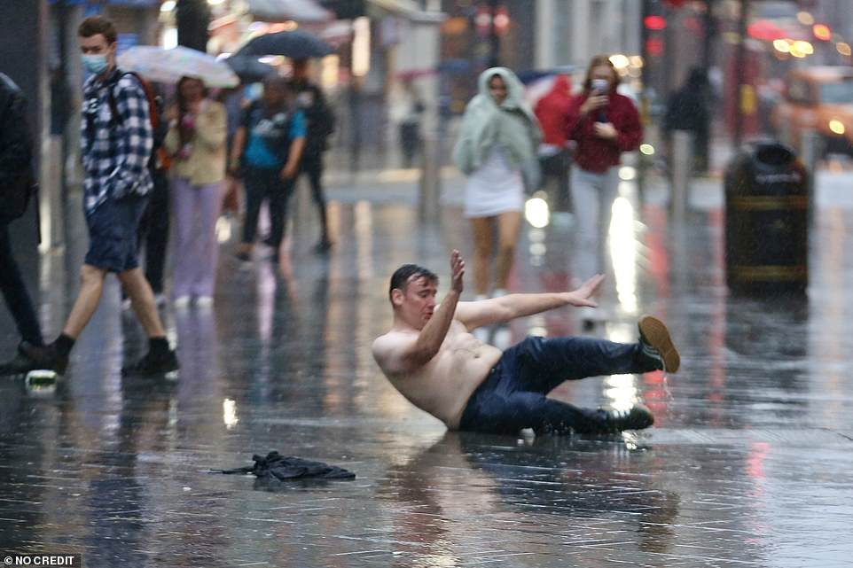 A topless Scotland football supporter falls over in the pouring rain in Leicester Square, central London , last night
