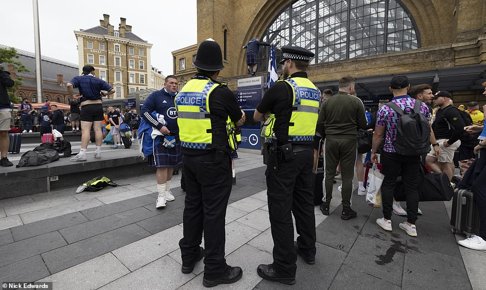 Hundreds of Met Police officers will form a ring of steel at Wembley to prevent ticketless fans accessing the stadium. Pictured: Police at King's Cross Station as fans arrived yesterday