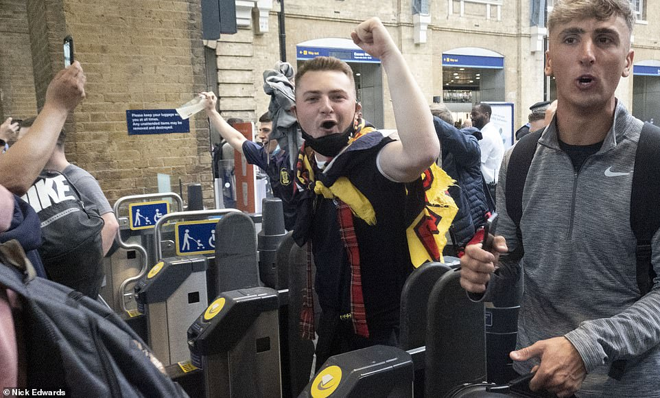 Football fans cheered as they exited through the turnstiles in King's Cross Station in London yesterday