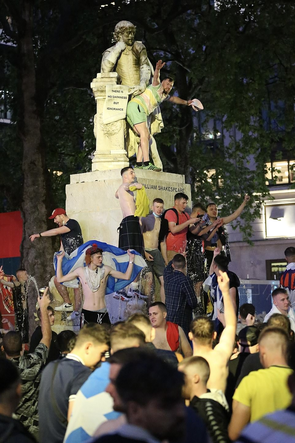 Scotland football fans climb the Shakespeare fountain in Leicester Square last night in London ahead of the Uefa clash