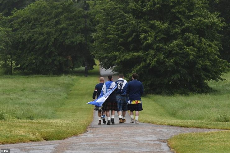 Four patriotically dressed Scottish fans make their way through a wet Hyde Park this morning ahead of the big game