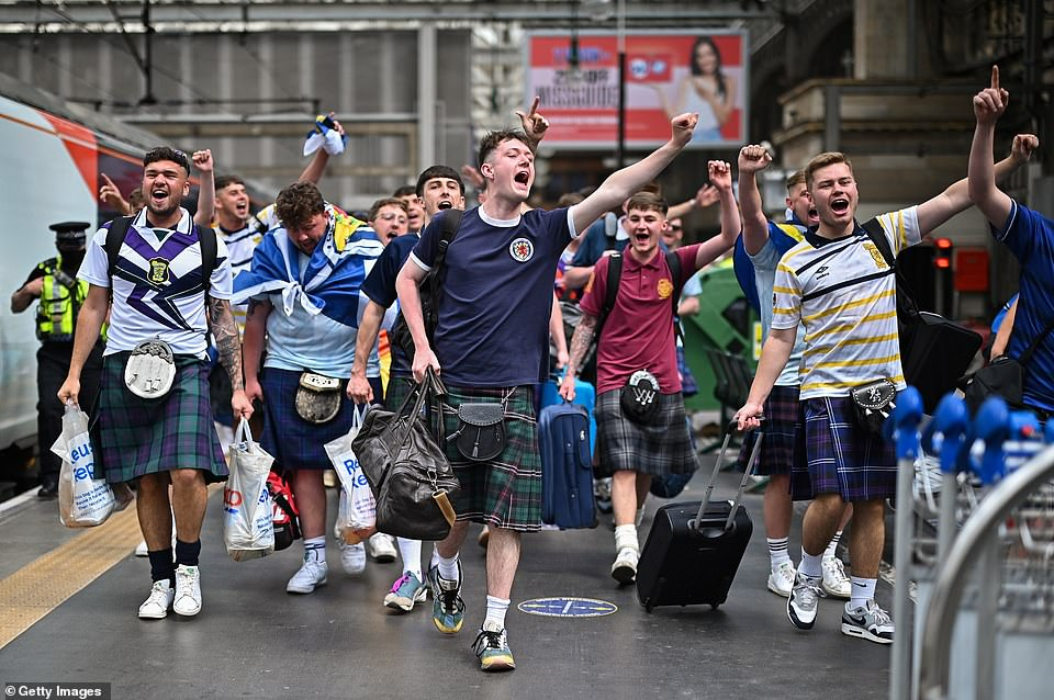Fans wearing kilts chanted and punched the air as they walked down the platform in Glasgow yesterday