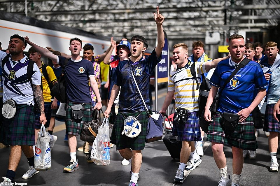 Scotland supporters were seen chanting as they made their way along the platform in Glasgow before boarding the train to London yesterday