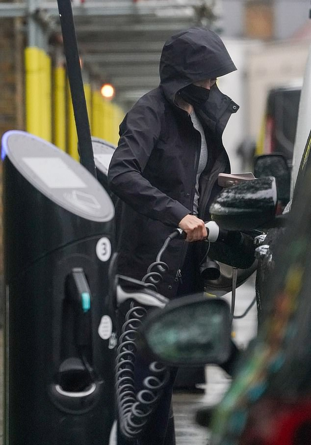 Carbon Conscious: Holly plugged her eco-friendly car into a roadside charging station as it continued to drizzle in the capital