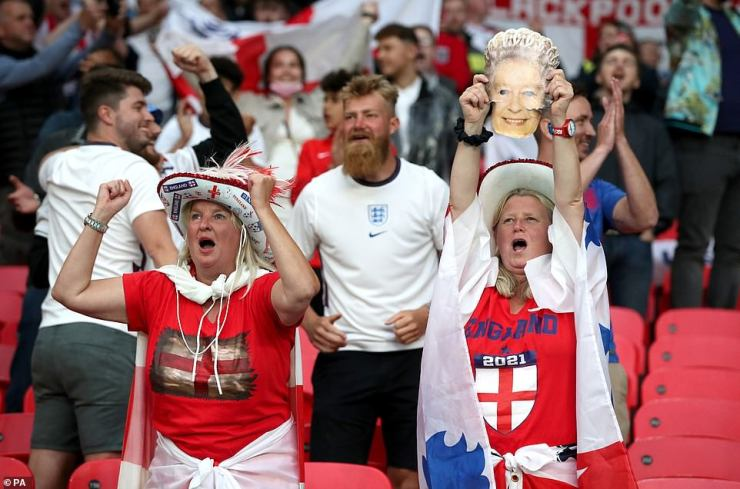 One female England fan holds up a picture of the Queen while another dons a cowboy hat as they cheer on their national team