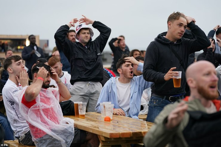 Fans react after a shot on goal as they watch the England v Scotland UEFA Euro 2020 match at the Hastings Pier fan zone