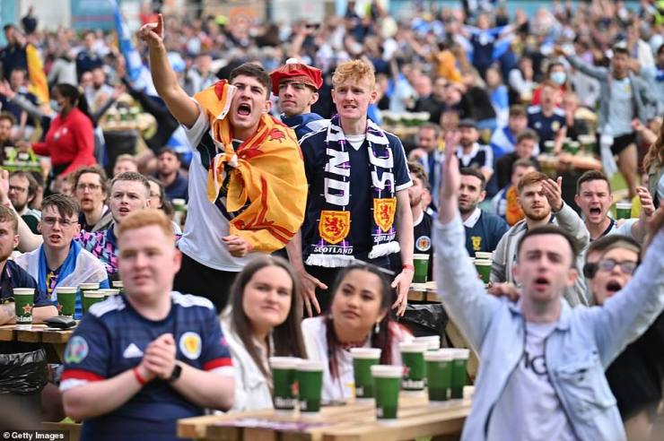 Scotland fans cheer as they support their team in the Euro 2020 game against England on June 18, 2021 in Glasgow