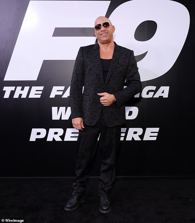 Standing out:Vin looked dapper in a stylish black suit covered in a textured floral pattern