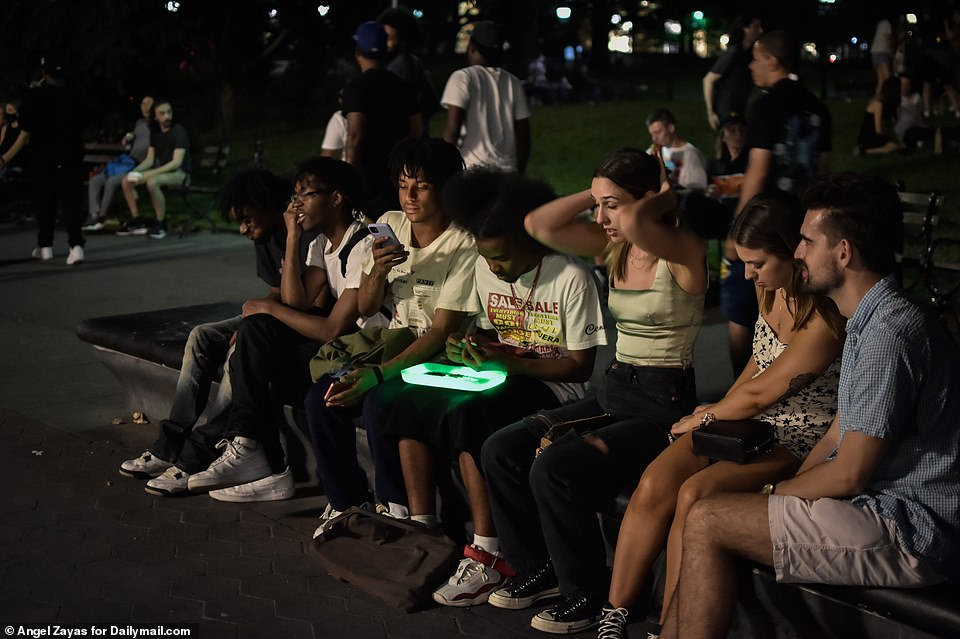A group of young people gather inside the park which has become a growing site of tension between local residents and partygoers in recent weeks