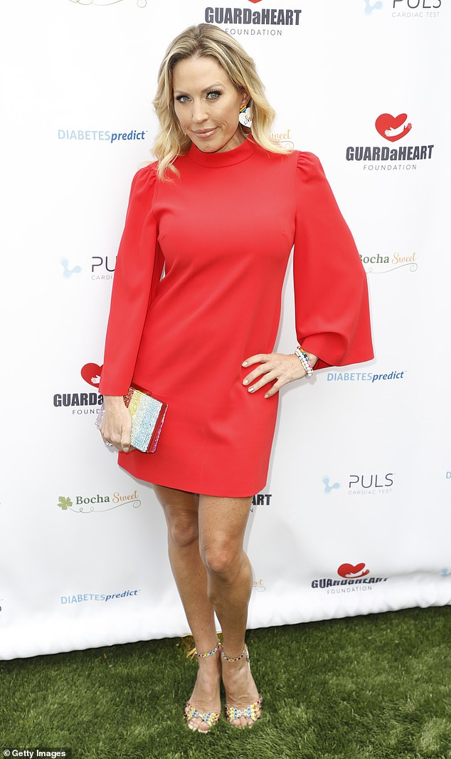 Own the color: Windham-Burke, 43, cut a young and elegant figure in an orange-red mini dress, falling to mid-thigh, with matching heels and a clutch