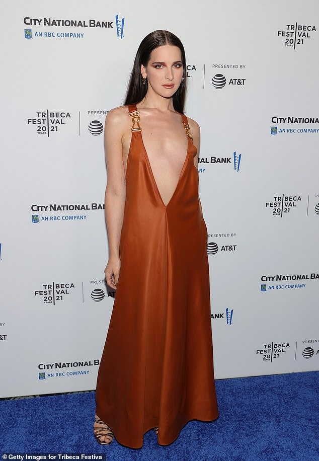 Flame-like Elegance: Beauty Hari Nef was there, in a stunning burnt hers dress with a deep plunging neckline and gold buckled straps