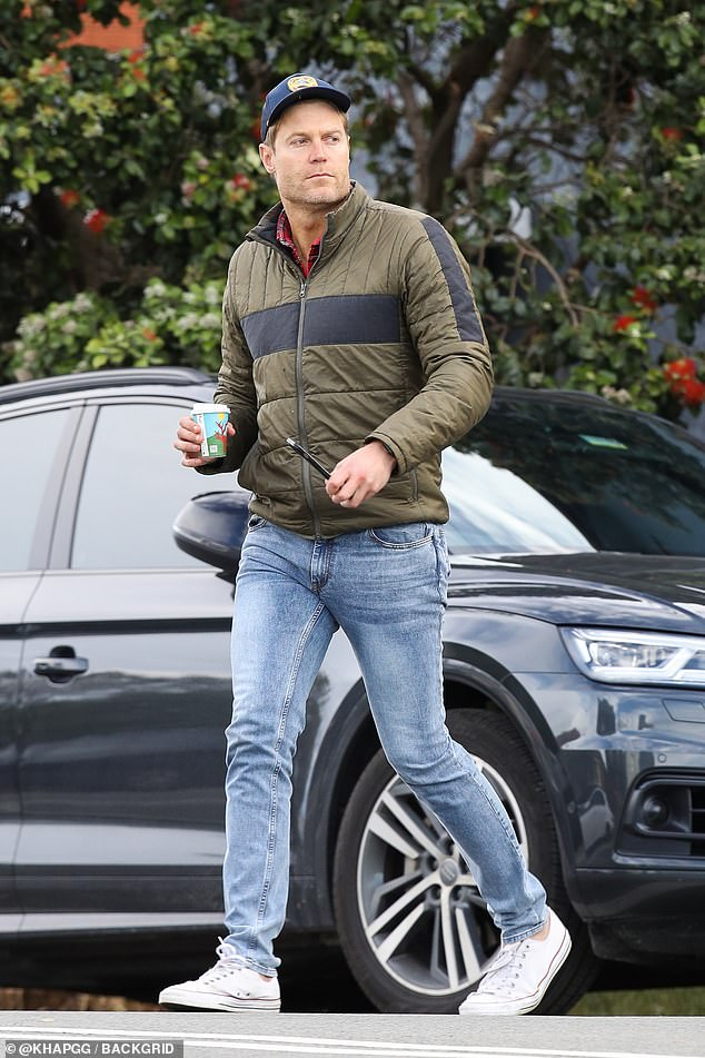 On the go: TV vet Dr Chris Brown kept warm in a padded jacket and jeans as he ate breakfast at a Sydney cafe on Friday