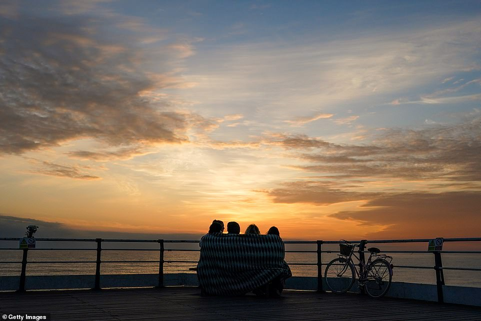A group of friends sit and watch the sunrise on the morning of the summer solstice at Saltburn