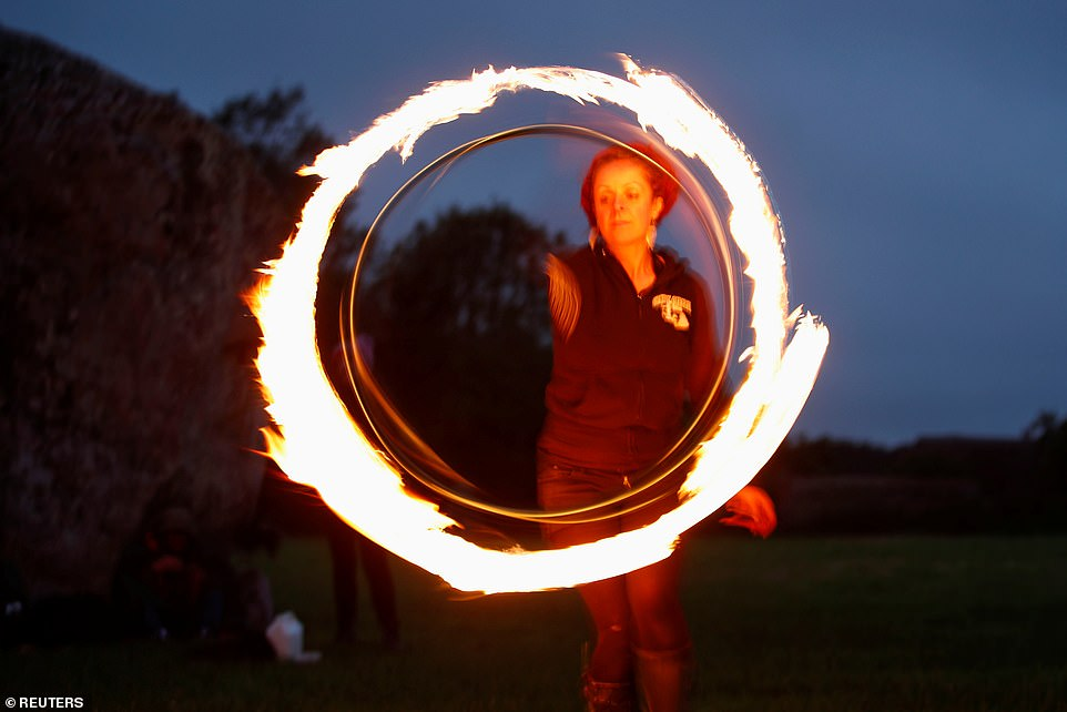 A person performs with fire during the celebration of the Summer Solstice, despite events being cancelled