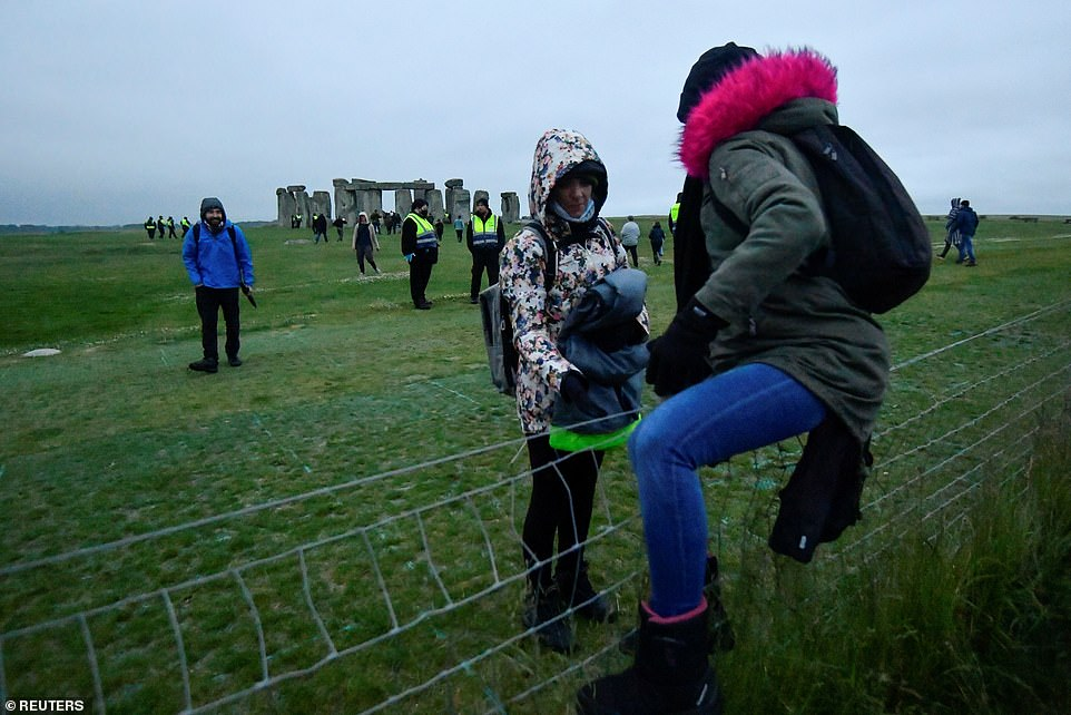 Revellers climb over a fence to get into Stonehenge ancient stone circle during the Summer Solstice celebrations