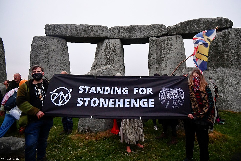 Revellers hold a banner at Stonehenge ancient stone circle during the Summer Solstice celebrations