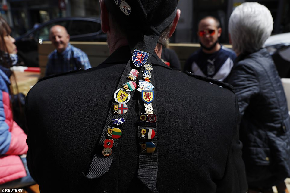A Scotland fan sports a series of badges as supporters gather in Glasgow this afternoon ahead of the Euro 2020 match