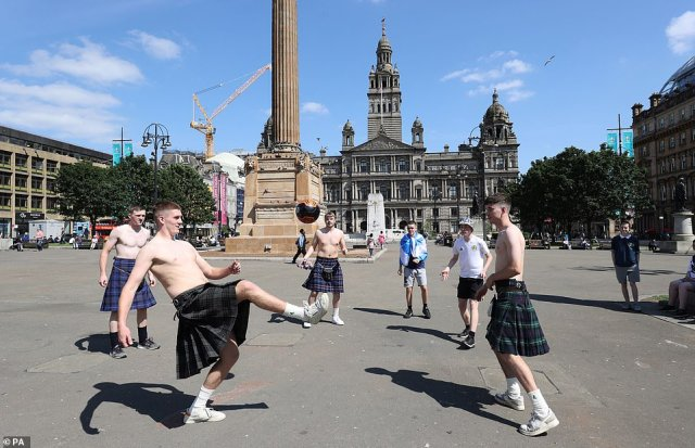 Sun's out kilts out: Shirtless fans enjoy a kickabout in traditional Scottish attire in the centre of Glasgow in anticipation for tonight's potentially historic match