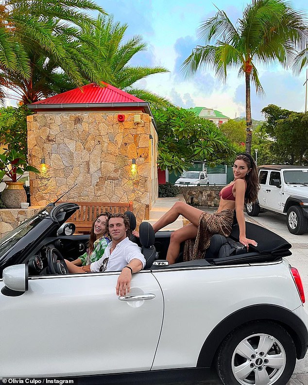 Fun in a convertible: Sophia sits next to her beau as Olivia takes the backseat