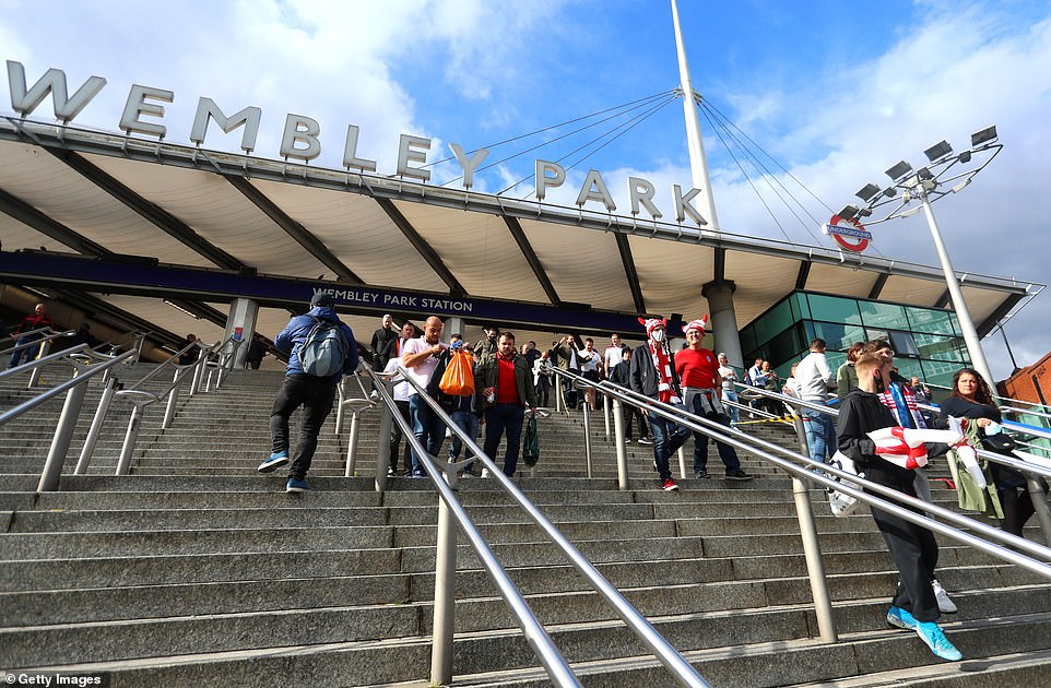 Fans arrive at Wembley Park tube station as they prepare to stroll along Wembley Walk to the stadium ahead of tonight's 8pm kick off