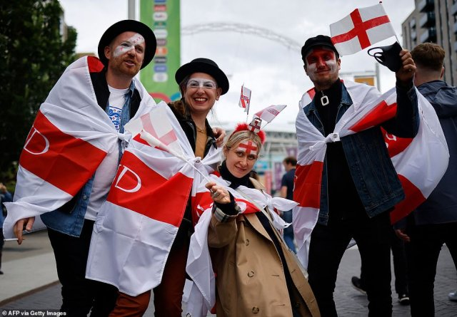 Three Lions fans draped in England flags prepare to take up their seats at Wembley ahead of tonight's game against Czech Republic