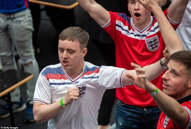 Three Lions fans touch the England badge after Raheem Sterling puts his side 1-0 up against the Czech Republic at Wembley
