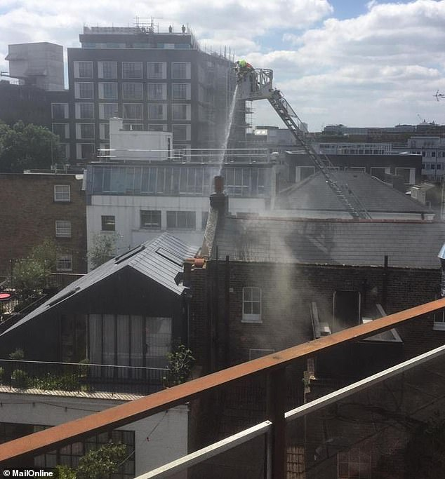 Firefighters rose above the building to pour water on the blaze, appearing to focus their efforts on the chimney area
