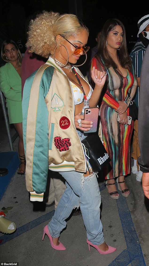 Stylish entrance: Saweetie looked sensational as she put on a busty display in a white bikini top that she wore with a pair of distressed denim jeans