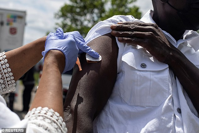 Researchers at the NIH estimate that 17 million Americans caught Covid in the early months of the pandemic. Pictured: A Detroit resident gets vaccinated in June 2021