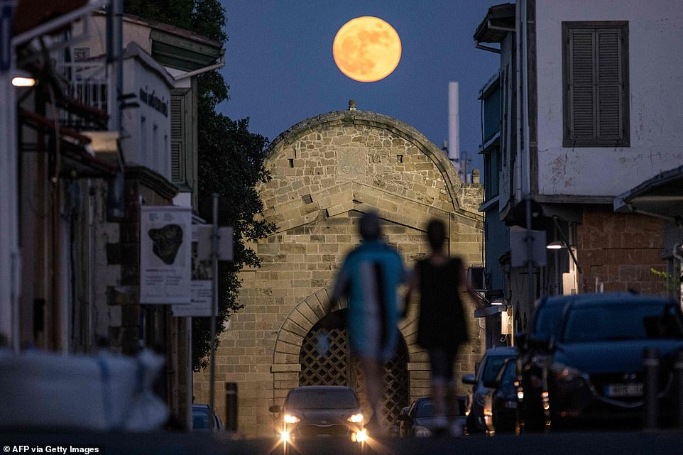 People walk beneath the rising Strawberry super moon towards the Venetian-built Famagusta gate in the old walled city of Cyprus' capital Nicosia on June 24, 2021