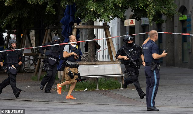 The suspect was identified as a 24-year-old Somali immigrant, who was shot in the leg by police and arrested after the attack in Wurzburg, Germany. Pictured: German police in action at the scene on Friday