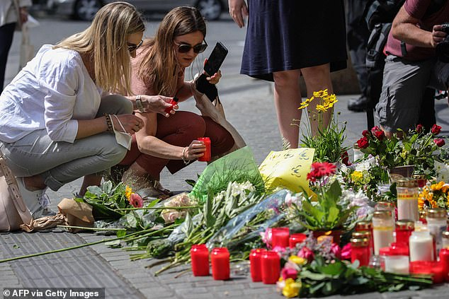 Among the three dead in the knife attack was a young boy and one of his parents, according to Main Post newspaper. Pictured: Women place a candle at the makeshift memorial