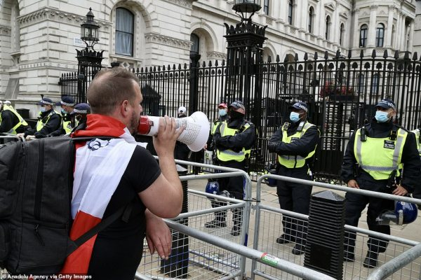 A demonstrator uses a megaphone to make his point to police as they stand guard outside 10 Downing Street