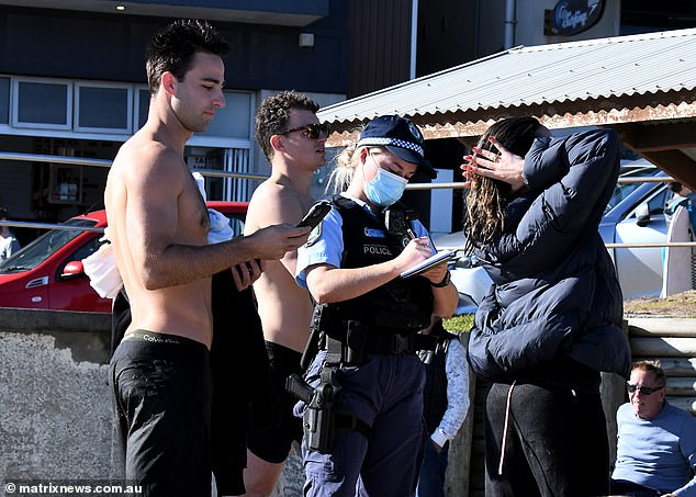A police officer at Bondi beach speaks with residence as she enforces Covid compliance (pictured on Sunday) as lockdown began in Sydney