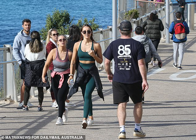 The host of cases were sparked by a limo driver in his 60s, who tested positive for Covid on June 16 - the first locally-acquired case in about 60 days at the time (pictured, walkers on Bondi Beach as lockdown began for Greater Sydney on Sunday)