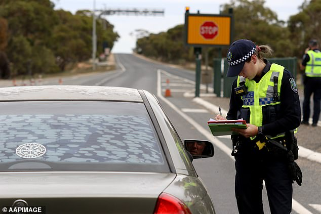 Police are seen at the border in South Australia at Pinnaroo near Victoria (pictured) as it slammed the border shut to most other states and territories