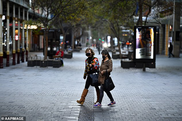 Pedestrians wearing face masks in the deserted central area of Sydney on Monday