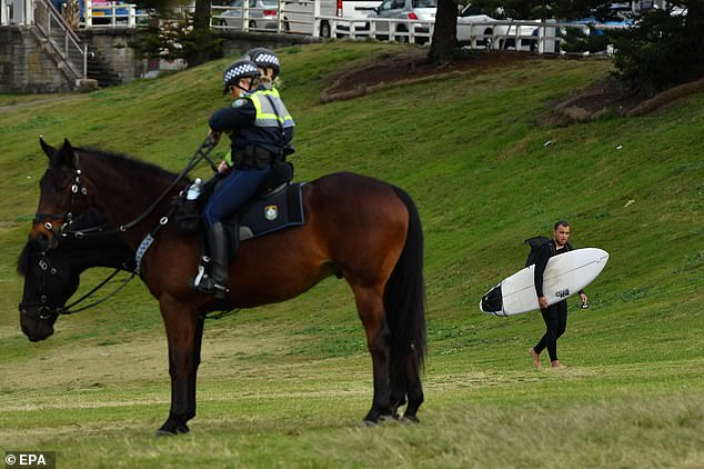 Mounted Police patrol as a surfer walks on the grass at Bondi Beach amid touch new lockdown restriction in Sydney on Monday