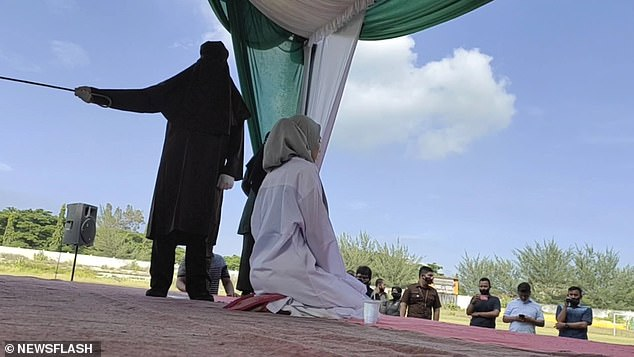 In the footage, the woman can be seen on a raised stage, wearing white robes and a headscarf and surrounded by officials and people filming on phones