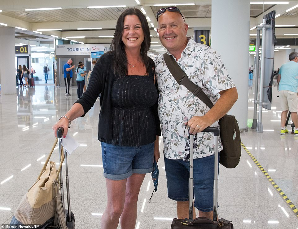 Hellen and David from London smile as they arrive at Palma Airport in Mallorca as Balearic Islands are on the UK 'green list'