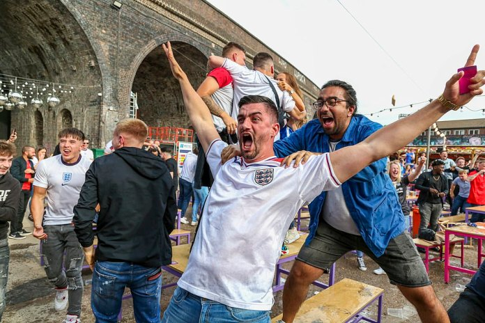England football fans celebrated their 2-0 victory against Germany yesterday in pubs, bars and in the street. Scientists have raised concerns that this could accelerate England's cases further. (Pictured: Three Lions supporters celebrate in Digbeth, Birmingham)