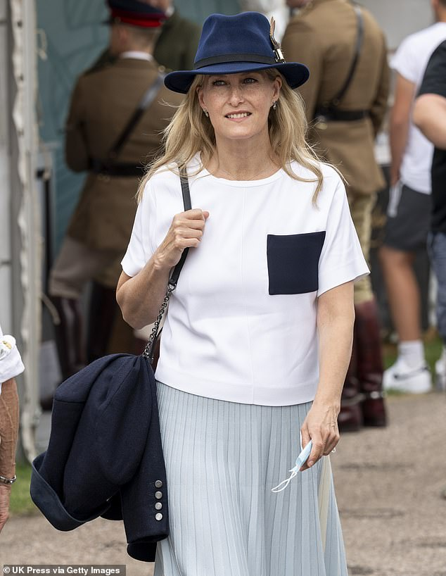 The royal made sure she had her sanitary mask in hand as she strolled around the horse show today