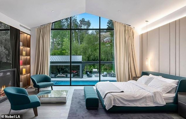 Room with a view: There are seven spacious bedrooms, including the master bedroom on the second floor (pictured) which overlooks the pool, as well as eight bathrooms